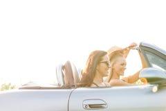 Amigos fêmeas felizes que apreciam a viagem por estrada no convertible contra o céu claro Imagem de Stock Royalty Free