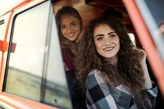 Amigos fêmeas novos em um roadtrip através do campo, olhando fora da carrinha fotografia de stock
