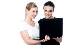 Amigos fêmeas novos felizes que usam o portátil Foto de Stock Royalty Free