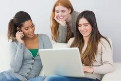 Amigos fêmeas novos felizes que usam o portátil e o telefone celular foto de stock