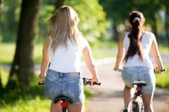 Amigos fêmeas novos que montam bicicletas Imagens de Stock