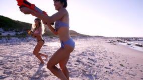 Amigos fêmeas novos que têm o divertimento na praia com luta da arma de água video estoque