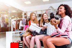 Amigos fêmeas positivos felizes com assento novo com sapatas e as caixas novas em seu regaço na loja da roupa fotografia de stock royalty free