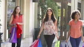 Amigos fêmeas que andam através da alameda com sacos de compras video estoque