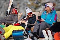 Amigos fêmeas que apreciam a bebida quente no café na estância de esqui sunbath imagens de stock royalty free