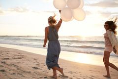 Amigos fêmeas que correm na praia com balões foto de stock royalty free