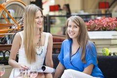 Amigos fêmeas que têm o almoço junto na alameda Foto de Stock