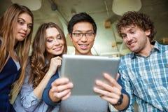 Amigos felices alegres positivos que usan la tableta Imagen de archivo