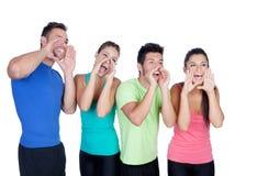 Amigos felices con el grito coloreado de la ropa de deportes Fotos de archivo libres de regalías