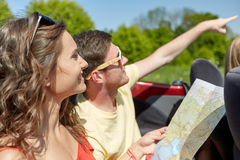 Amigos felices con el mapa que conduce en coche del cabriolé Fotos de archivo libres de regalías