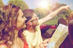 Amigos felices con el mapa que conduce en coche del cabriolé Foto de archivo