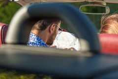 Amigos felices con el mapa que conduce en coche del cabriolé en el país y que señala el finger algo a continuación Fotografía de archivo