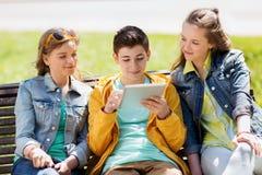 Amigos felices con el ordenador de la PC de la tableta al aire libre Imagen de archivo libre de regalías