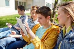 Amigos felices con el ordenador de la PC de la tableta al aire libre Foto de archivo libre de regalías