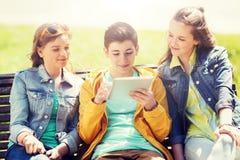Amigos felices con el ordenador de la PC de la tableta al aire libre Foto de archivo