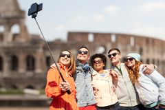 Amigos felices con el palillo del selfie del smartphone Imágenes de archivo libres de regalías