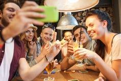 Amigos felices con el smartphone que toma el selfie en la barra Foto de archivo libre de regalías