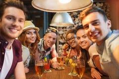 Amigos felices con el smartphone que toma el selfie en la barra Fotografía de archivo