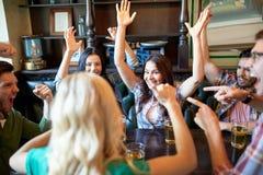 Amigos felices con la cerveza que celebran en la barra o el pub Imagen de archivo