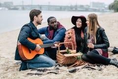 Amigos felices con la guitarra en la comida campestre al aire libre Imagenes de archivo