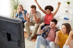 Amigos felices con la TV de observación remota en casa Fotografía de archivo libre de regalías