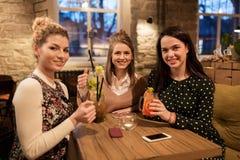 Amigos felices con las bebidas en el restaurante Imágenes de archivo libres de regalías