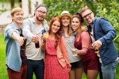 Amigos felices con las bebidas en la fiesta de jardín del verano Imagen de archivo
