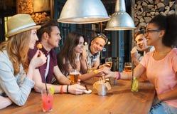 Amigos felices con las bebidas que hablan en la barra o el pub fotografía de archivo