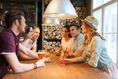 Amigos felices con las bebidas que hablan en la barra o el pub Fotos de archivo libres de regalías