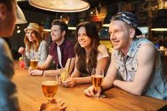 Amigos felices con las bebidas que hablan en la barra o el pub Imagen de archivo libre de regalías