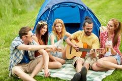 Amigos felices con las bebidas y guitarra en acampar Fotografía de archivo
