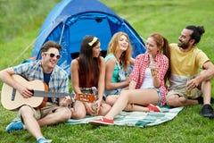 Amigos felices con las bebidas y guitarra en acampar Imagen de archivo