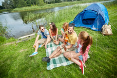 Amigos felices con las bebidas y guitarra en acampar Fotos de archivo libres de regalías