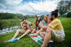 Amigos felices con las bebidas y guitarra en acampar Imagenes de archivo