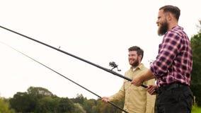 Amigos felices con las cañas de pescar metrajes