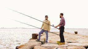 Amigos felices con las cañas de pescar en el embarcadero almacen de metraje de vídeo