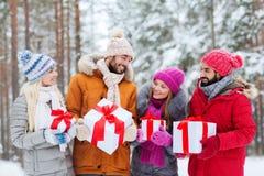 Amigos felices con las cajas de regalo en bosque del invierno Imagenes de archivo