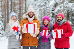 Amigos felices con las cajas de regalo en bosque del invierno Imágenes de archivo libres de regalías