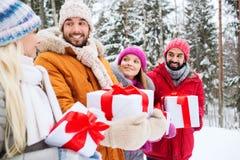 Amigos felices con las cajas de regalo en bosque del invierno Fotos de archivo libres de regalías