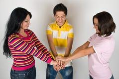 Amigos felices con las manos unidas Imagen de archivo libre de regalías