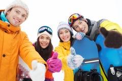 Amigos felices con las snowboard que muestran los pulgares para arriba Foto de archivo libre de regalías