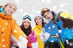 Amigos felices con las snowboard que muestran los pulgares para arriba Foto de archivo
