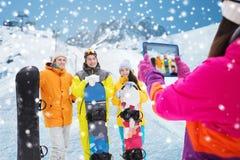 Amigos felices con las snowboard y PC de la tableta Imágenes de archivo libres de regalías