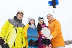 Amigos felices con las snowboard y smartphone Imágenes de archivo libres de regalías