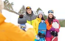 Amigos felices con las snowboard y smartphone Fotografía de archivo libre de regalías