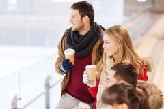 Amigos felices con las tazas de café en pista de patinaje Foto de archivo libre de regalías