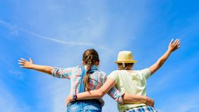 Amigos felices con los brazos abiertos debajo del cielo azul Fotos de archivo libres de regalías