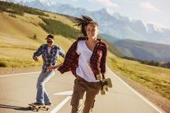 Amigos felices con los patines y longboards en el camino recto foto de archivo libre de regalías