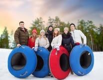 Amigos felices con los tubos de la nieve al aire libre en invierno foto de archivo libre de regalías
