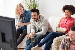 Amigos felices con palomitas que ven la TV en casa Fotografía de archivo libre de regalías